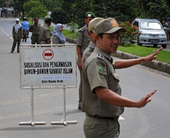 Indonesia Islam police of Aceh sharia manning a checkpoint as they flag down female motorists wearing tight pants and skirts in Dec. 09. Until now the violations have  resulted in only temporary holdings, now they could face weeks of detention.  (Romeo Gacad/Getty Images)