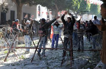 Residents from the central Tunisian region of Sidi Bouzid clash with security forces on January 26, 2011 in front of Prime Minister Mohammed Ghannouchi's office in Tunis.  Tunisia said January 26 it had issued an international arrest warrant for Ben Ali,  (Fethi Belaid/AFP/Getty Images)