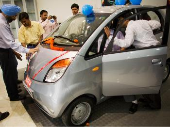 The world's cheapest car, A Tata Nano is inspected by members of the public on display in a Tata showroom in New Delhi, India.   (Daniel Berehulak/Getty Images)