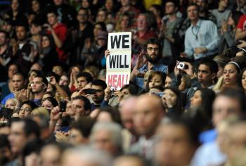 An attendee displays a placard that says 'We Will Heal!' during the memorial event, 'Together We Thrive: Tucson and America', at the McKale Memorial Center in Tucson, Arizona, on Jan. 12. (JEWEL SAMAD/AFP/Getty Images)