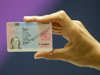 A British Home Office employee displays an official British biometric ID card at a press conference in London, on September 25, 2008.    (Shaun Curry/AFP/Getty Images)