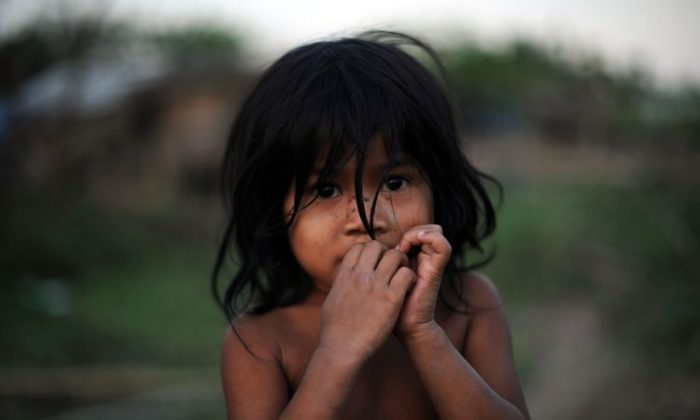 A child poses for a picture on the outskirts of Myanmar's biggest city Yangon on Feb.21 2011. (STR/AFP/Getty Images)