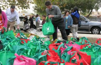 Children and parent volunteers for CHPHP deliver 'Thanksgiving In A Bag' gifts for the homeless people in their community. (Courtesy of CHPHP)