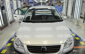 Volkswagen employees work on cars on the assembly line of the plant in Sao Paulo. (Michael Kappeler/AFP/Getty Images)
