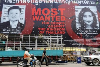 An anti-government poster depicting former Thai prime minister Thaksin Shinawatra and his wife Pojjaman in front of the United Nations office near Government House in Bangkok. The Thai government is seeking the extradition of former the Thai prime minister.  (Saeed Khan/Getty Images)