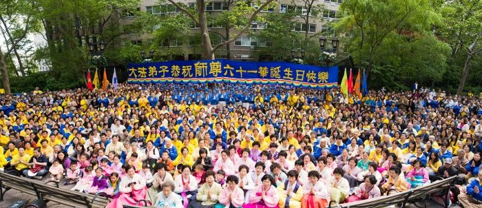 Outside the United Nations building in New York City on May 11, two Falun Gong practitioners hold a banner emblazoned with the core principles of this spiritual practice: truthfulness, compassion, and tolerance. In the background, hundreds of practitioners meditate. The event is part of a celebration of the 20-year anniversary of the introduction of Falun Gong in China. (Epoch Times Staff).