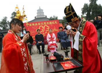 LINKED BY DESTINY: A newly wed couple dressed in traditional Han costumes drinks wine from a pair of cups linked by a red thread in Xian city, China. The legend of the red thread has evolved into a mulitude of traditions. (China Photos/Getty Images)