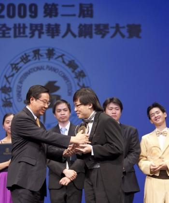 Gold winner Xiaofeng Wu accepts his award from NTDTV President Zhong Lee. (Edward Dai/The Epoch Times)