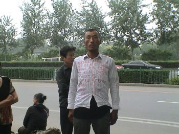 This man wrote out his grievances on his shirt. (The Epoch Times)