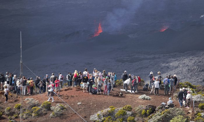 "Volcano-watchers gather on an overlooking vantage point as lava erupts from the Piton de la Fournaise ""Peak of the Furnace"" volcano, on the southeastern corner of the Indian Ocean island of Reunion Saturday, Aug. 1, 2015. Spewing red-hot lava, one of the most active volcanoes in the world is currently erupting on this Indian Ocean island, where the world's attention has been focused since a wing fragment believed to be from the missing Malaysian jet was discovered washed up on a beach. (AP Photo/Ben Curtis)"