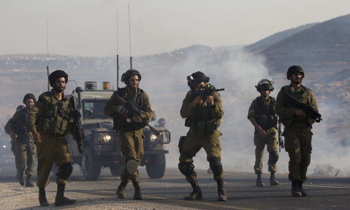 Israeli soldiers clash with Palestinians at the entrance of Duma village near the West Bank city of Nablus, Saturday, Aug. 1, 2015.  (AP Photo/Majdi Mohammed)