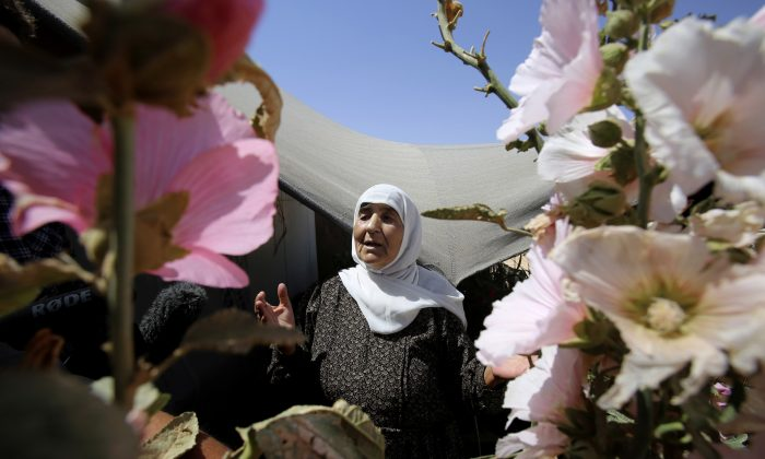 In this Wednesday, July 29, 2015 photo, an elderly Syrian refugee woman stands outside her shelter surrounded with flowers she planted, at Zaatari refugee camp, in Mafraq, Jordan. (AP Photo/Raad Adayleh)