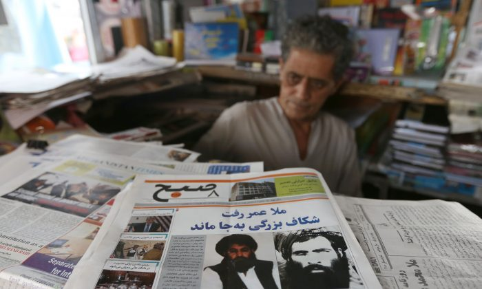 An Afghan store clerk waits for customers at a news stand where local papers carry headlines about the new leader of the Afghan Taliban, Mullah Akhtar Mohammad Mansoor, in Kabul, Afghanistan, Saturday, Aug. 1, 2015. The new leader of the Afghan Taliban vowed to continue his group's bloody, nearly 14-year insurgency in an audio message released Saturday, urging his fighters to remain unified after the death of their longtime leader. (AP Photo/Rahmat Gul)