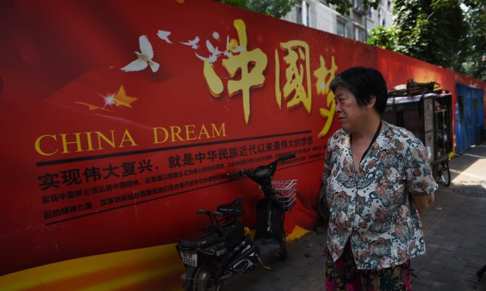 """A woman looks at a banner about the """"China Dream"""", Chinese President Xi Jinping's vision for China's future, in Beijing on July 7, 2015. (Greg Baker/AFP/Getty Images)"""