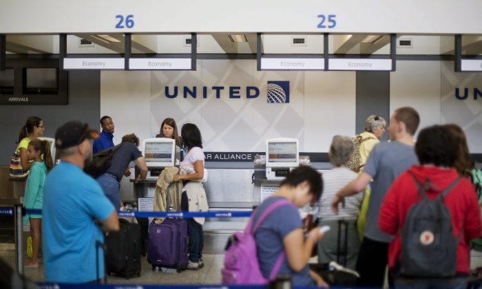 Travelers line up at a United Airlines check-in counter at Hartsfield–Jackson Atlanta International Airport Wednesday, July 8, 2015, in Atlanta. All United Continental flights in the U.S. were grounded Wednesday due to computer problems. Just shy of two hours after the problems began, the Federal Aviation Administration lifted the ground stop order.  (AP Photo/David Goldman)