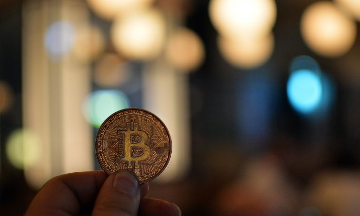 A man holds a bitcoin medal as members of bitcoin trading club hold a meeting in Tokyo on February 27, 2014. (YOSHIKAZU TSUNO/AFP/Getty Images)