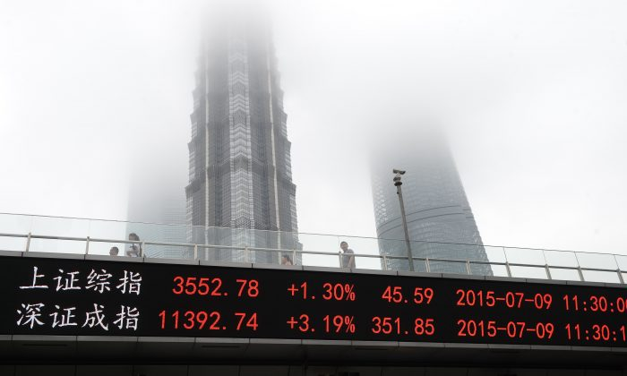 A screen showing the Shanghai Composite Index (top) and the Shenzhen Component Index on the side of an overpass in front of the Shanghai World Financial Center (L), Jin Mao Tower (C) and Shanghai Tower in Shanghai on July 9, 2015. (STR/AFP/Getty Images)