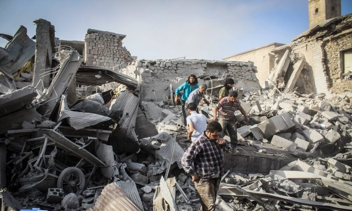 This photo provided by the Syrian anti-government activist group Ariha Today, which has been authenticated based on its contents and other AP reporting, shows Syrian citizens looking for survivors after a government warplane crashed in the center of the town of Ariha, in the northwestern province of Idlib, Syria, Monday, Aug. 3, 2015. Air raids and the subsequent crash of a Syrian warplane in a residential area in the northwestern town of Ariha on Monday killed and wounded dozens of people, two activist groups said. (Ariha Today via AP)