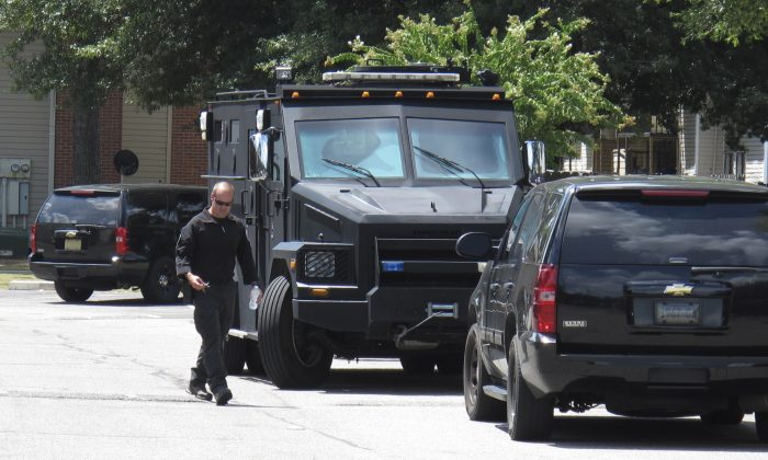 A police officer walks by an armored truck during a search of an apartment complex on Sunday, Aug. 2, 2015, in Memphis, Tenn. (AP Photo/Adrian Sainz)