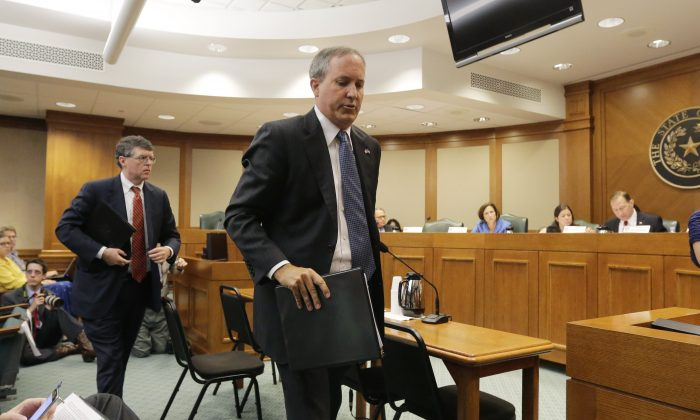 Texas attorney general Ken Paxton, right, with his chief of staff Bernie McNamee, left, departs after he testified during a Texas Texas Senate Health and Human Services Committee hearing on Planned Parenthood videos covertly recorded that target the abortion provider, Wednesday, July 29, 2015, in Austin, Texas. (AP Photo/Eric Gay)