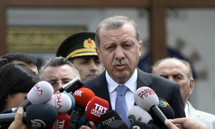 "Turkish President Recep Tayyip Erdogan speaks to the media in front of a mosque in Istanbul, Turkey, on July 24, 2015. In a major tactical shift, Turkish warplanes struck Islamic State targets across the border in Syria on July 24, Turkish officials announced—a move that came a day after ISIS militants fired at a Turkish military outpost, killing a soldier. In a related, long-awaited development, Erdogan confirmed that Turkey had agreed to let the United States use a key base in southern Turkey for military operations against the militants ""within a certain framework."" (Depo Photos/AP)"