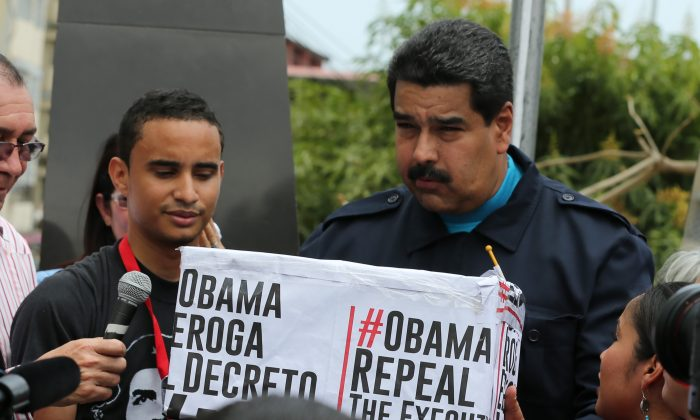 Venezuela's President Nicolas Maduro (R) holds a box covered by hashtags that contains signatures from supporters who signed a petition asking the U.S. to end sanctions against Venezuela during a ceremony in the neighborhood of Chorrillo in Panama City on April 10, 2015. Maduro has become the third most-retweeted public figure in the world, behind Pope Francis and the King of Saudi Arabia, according to public relations firm Burston Marsteller. But a closer look suggests that the government is artificially inflating its social media pull by using networks of fake accounts. (AP Photo/Ramon Espinosa)