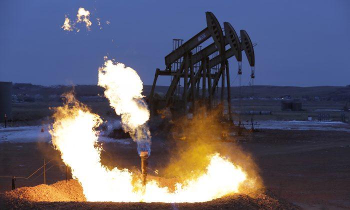 Oil pump jacks work behind a natural gas flare near Watford City, N.D., on Dec. 17, 2014. (Eric Gay/AP Photo)