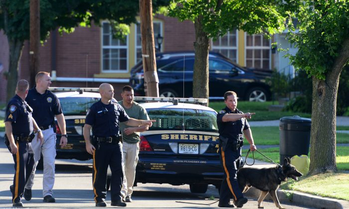 Little Falls Police and a Passaic County Sheriff Department K-9 Unit conduct a search for a burglary suspect on Lincoln Ave, Wednesday, July 22, 2015, in Little Falls, NJ. (Tariq Zehawi/The Record of Bergen County via AP)