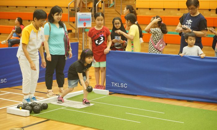 Hong Kong Lawn Bowls Association coach YY Wu teaching kids the basics of lawn bowls at the Sport for All Day event at Tiu Keng Leng Sports Centre on Sunday Aug 2. (Claudius Lam)