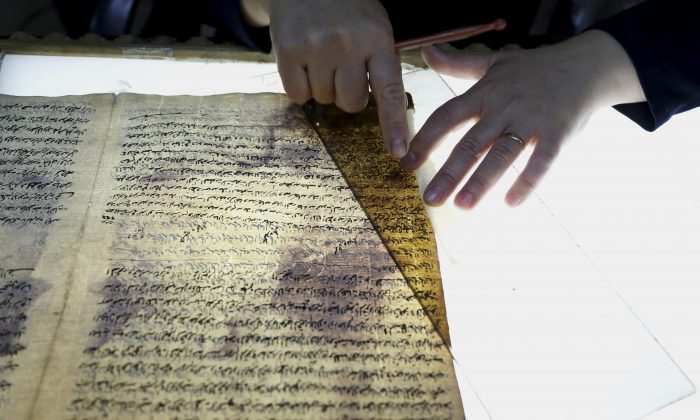 In this Tuesday, July 28, 2015 photo, a member of the library restoration staff works on a damaged document at the Baghdad National Library in Iraq. (AP Photo/Karim Kadim)