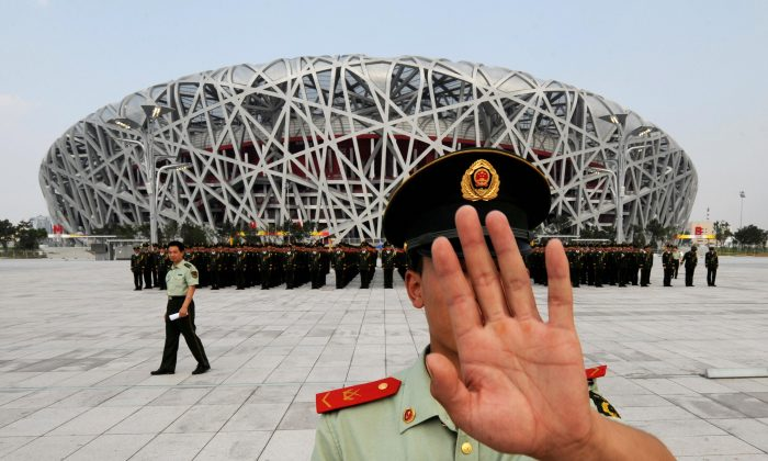 A Chinese paramilitary policeman tries to block photos being taken of a military parade rehearsal, outside the Olympic Stadium in Beijing on  July 21.  (Mark Ralston/AFP/Getty Images)