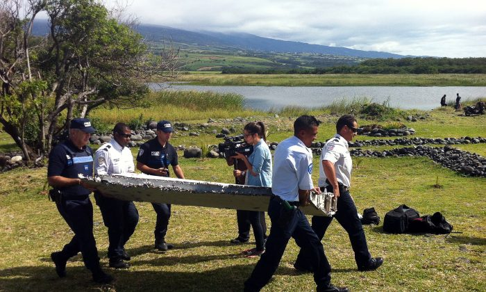 Police carry a piece of debris found in the coastal area of Saint-Andre de la Reunion, in the east of the French Indian Ocean island of La Reunion, which has been identified as part of missing Malaysian Air MH370 on July 29, 2015. (Yannick Pitou/AFP/Getty Images)