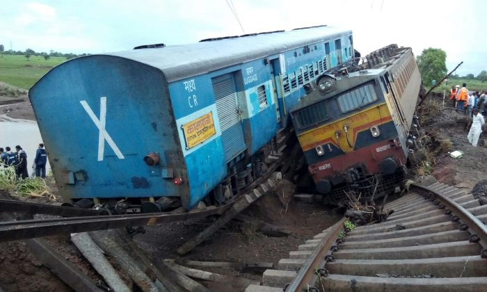 Two Indian passenger trains lay next to each other following a derailment after they were hit by flash floods on a bridge outside the town of Harda in Madhya Pradesh state on August 5, 2015. At least two dozen were killed in the latest deadly accident on the nation's crumbling rail network. (AFP/Getty Images)