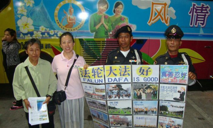 Two local police hold a Falun Gong banner, with two Falun Gong practitioners, in Bangkok, Thailand, 2010. (Epoch Times)
