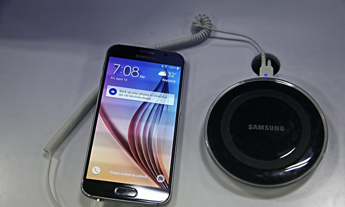 In this April 10, 2015 file photo,  the new Samsung Galaxy S6 smartphone is on display at a Best Buy electronics store in San Francisco. (AP Photo/Eric Risberg; effects added by Epoch Times)