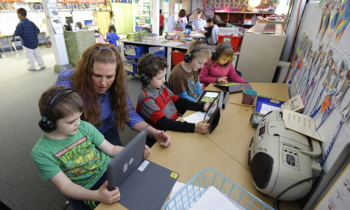 Teacher Haley Fazio (2nd L) works with her kindergarten students on a frog-research lesson viewed on tablet computer in Des Moines, Wash., on March 10, 2015. (AP Photo/Ted S. Warren)