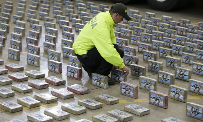 A police officer organizes rows of seized packages of cocaine during a police presentation for the press in Bogota, Colombia, on July 22, 2015. (AP Photo/Fernando Vergara)
