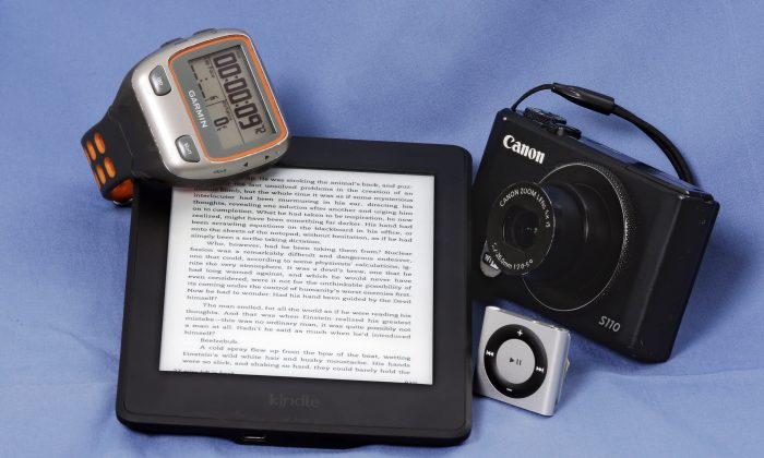 A Garmin Forerunner 310XT GPS Sports Running Multisports Speed & Distance Watch, an Amazon Kindle, Apple iPod Shuffle and a Canon S110 camera are arranged for a photo in New York, Tuesday, Aug. 4, 2015. (AP Photo/Richard Drew)