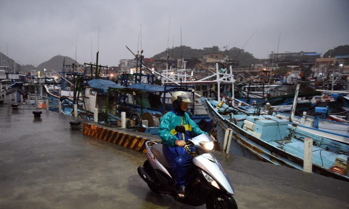 A man rides past fishing boats moored in a shelter at Nanfangao harbour in Yilan on August 6, 2015 as typhoon Soudelor approaches eastern Taiwan. The strongest typhoon of the year was bearing down on Taiwan's east coast on August 6, forcing the evacuation of more than 2,000 from outlying islands popular with tourists. (AFP/Getty Images)