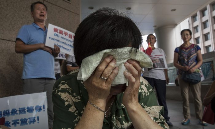 Bao Lanfang, a Chinese relative of missing passengers on Malaysia Airlines flight MH 370 cries as she waits for information outside the airline's office on August 6, 2015 in Beijing, China.  (Kevin Frayer/Getty Images)