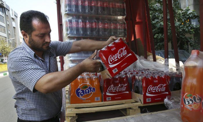 In this Wednesday, Aug. 5, 2015 photo, an Iranian worker adjusts bottles of Coca-Cola on a truck while delivering soft drink to shops in Tehran, Iran. (AP Photo/Vahid Salemi)