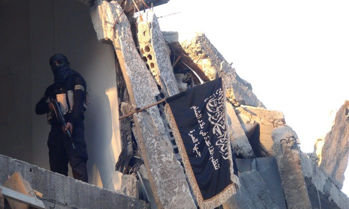 An extremist from ISIS is next to the group's flag in the south of Damascus, Syria, on Sept. 22, 2014. Terrorist recruiters bringing fighters to Iraq and Syria have been traced to locations in Russia and Eastern Europe. (Rami al-Sayed/AFP/Getty Images)