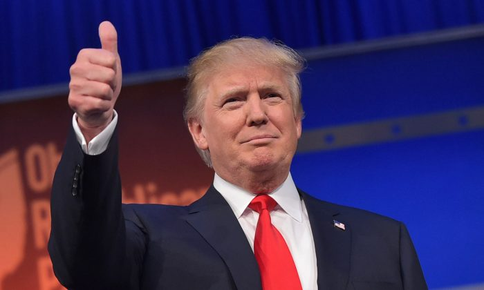 Real estate tycoon Donald Trump flashes the thumbs-up as he arrives on stage for the start of the prime time Republican presidential debate on August 6, 2015 at the Quicken Loans Arena in Cleveland, Ohio. (AFP/Getty Images)