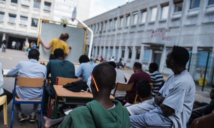 In this Thursday, Aug. 6, 2015 photo, Camille Arrignon, 23, from France gives a French lesson to the migrants on the grounds of the Guillaume-Bude secondary school building in Paris. For now, Paris is largely allowing associations to convert some vacant public buildings like this Paris high school into emergency lodging for around 200 migrants. (AP Photo/Kamil Zihnioglu)