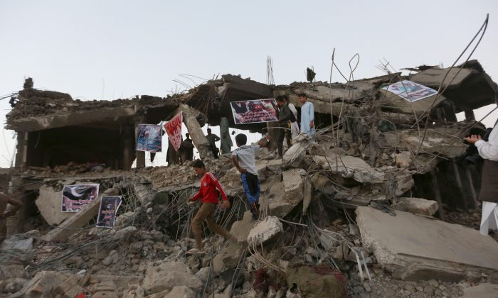 Afghan boys walk on debris of a market destroyed by the blast of Friday's truck bomb in Kabul, Afghanistan, Saturday, Aug. 8, 2015. (AP Photo/Rahmat Gul)