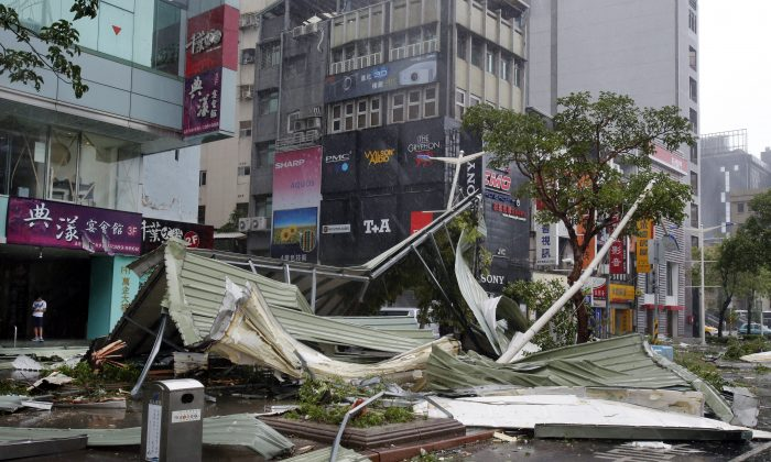 A mangled rooftop brought down by strong winds from Typhoon Soudelor covers a street corner in Taipei, Taiwan, Saturday, Aug. 8, 2015. Soudelor brought heavy rains with winds speeds over 170 km per hour (100 mph) and gusts over 200 km per hour (120 mph) according to Taiwan's Central Weather Bureau. (AP Photo/Wally Santana)