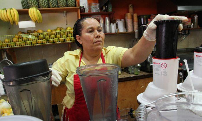 Celina Alvarez, 51, works at Jugueria de regreso al Eden, her shop in the Queens, New York, on Monday, Aug. 3, 2015. (AP Photo/Tina Fineberg)