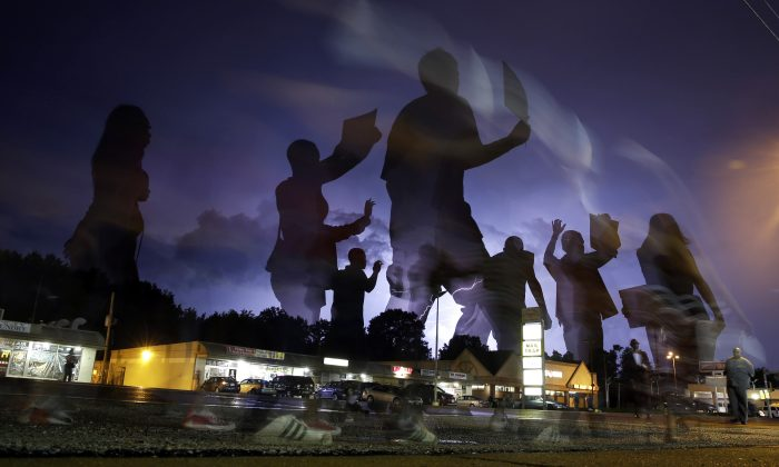 Photo taken with a long exposure, protesters march in the street as lightning flashes in the distance in Ferguson, Mo, Aug. 20, 2014. (AP Photo/Jeff Roberson)