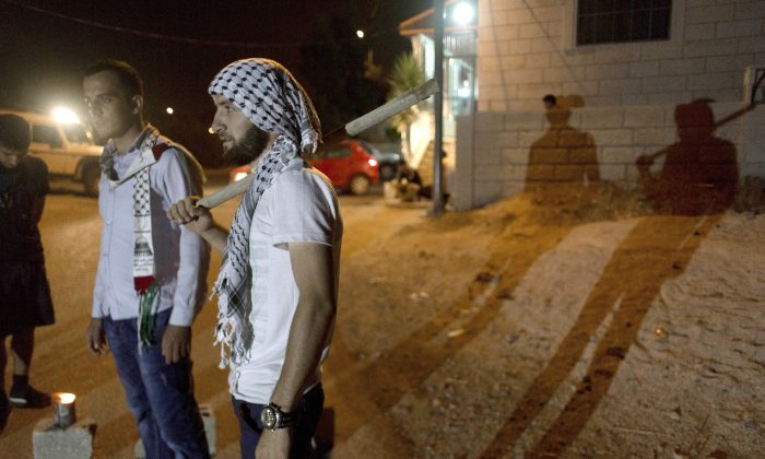 In this Tuesday, Aug. 4, 2015 photo, Palestinian villagers stand guard at the entrance of the West Bank village of al-Jab'a, near Bethlehem. The Residents of the village formed groups of defense volunteers to guard themselves from attacks of Israeli settlers. (AP Photo/Nasser Nasser)