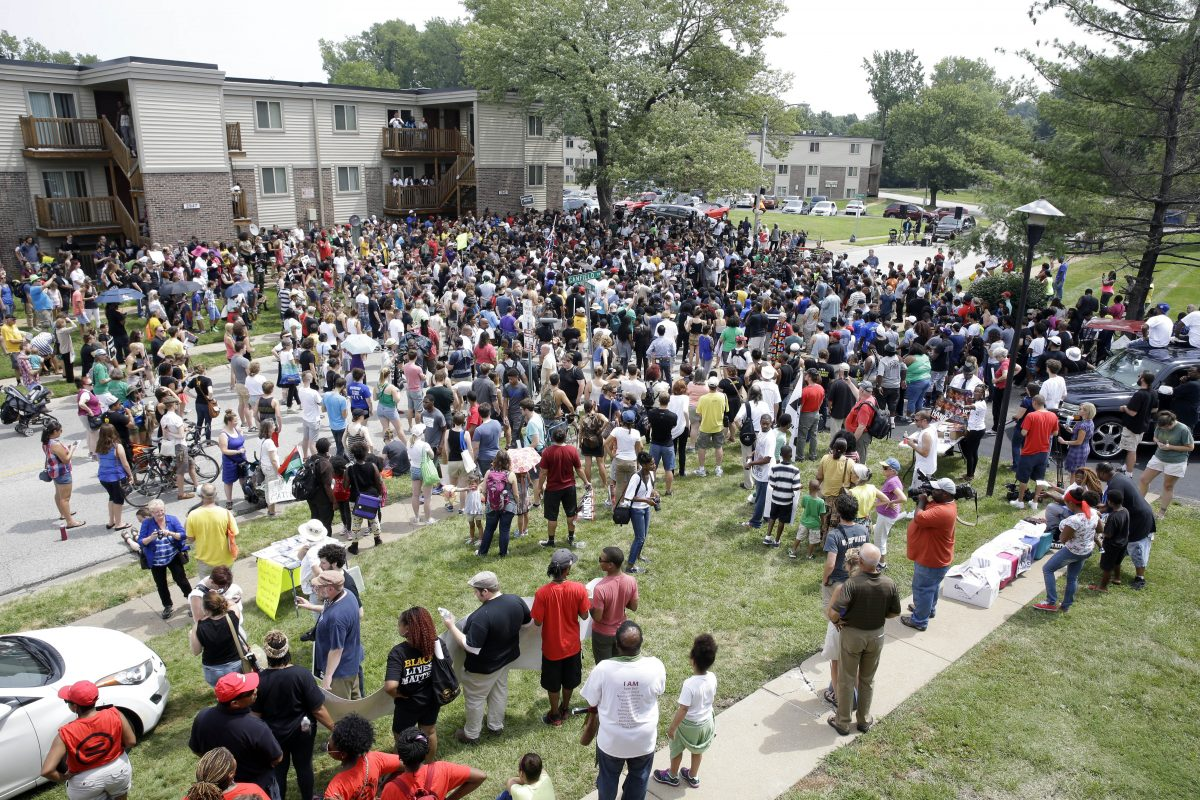 Several hundred people gather for a remembrance for Michael Brown in Ferguson, Mo., on Sunday, Aug. 9, 2015. Sunday marks one year since Michael Brown was shot and killed by Ferguson police officer Darren Wilson. (AP Photo/Jeff Roberson)